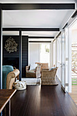 Open living room, rattan armchair in front of terrace door
