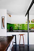Einbauküche mit grüner Rückwand, Barhocker an der Theke, im Vordergrund rustikaler Esstisch