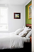 Double bed with wooden headboard on green wall in bedroom