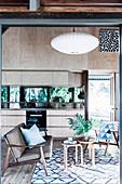 Offene Küche mit heller Holzfront und verspiegelter Rückwand, im Vordergrund Sitzbereich