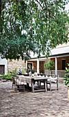 Rustikal gedeckter Gartentisch im sommerlichen Innenhof