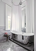 Shining silver freestanding bathtub in luxurious bathroom