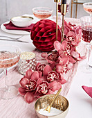 Centerpiece made of pink orchids on a festively laid table