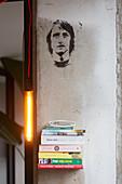 Wandregal mit Bücherstapel, Leuchte und Portrait an der Wand