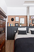 Double bed against black sideboard and brick wall in bedroom with antique chest of drawers in foreground