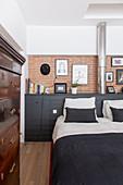 Doppelbett vor schwarzem Sideboard an Ziegelwand im Schlafzimmer, im Vordergrund Antik Kommode