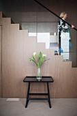 Tabletttisch mit Blumenstrauß vor Treppe mit Geländer aus Glas