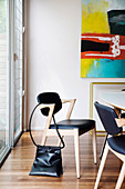 Designer chair with black leather upholstery around dining table
