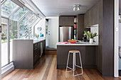 Elegant, dark fitted kitchen with breakfast bar, stainless steel fridge and window front