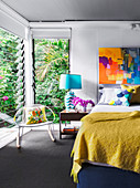 Double bed with mustard yellow bedspread, bedside table with blue table lamp and rocking chair in the bedroom, colorful artwork on the wall