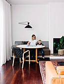 Mutter und Sohn sitzen auf eingebauter Sitzbank am runden Tisch im Wohnzimmer