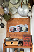 Pots and kitchen utensils hanging over rustic shelf