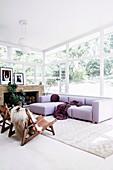 Lilafarbenes Sofa im Wohnzimmer mit umlaufender Fensterfront
