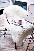 Cup and magazine on a chair with sheepskin