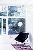 Schwarzer Designersessel und Bücher am Fenster zum Garten