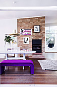 Violet upholstered bench at the dining table in front of the brick fireplace