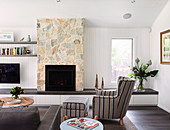 Living room with upholstered armchair, built-in bench and fireplace in sandstone wall