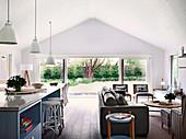 Kücheninsel mit Barhockern und Lounge mit Ledersofa und Rattanstühlen in offenem Wohnraum mit Terrassenzugang