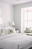 Double bed with white bedspread in white bedroom