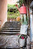 Bepflanzte Gießkannen aus Metall an einer mediterranen Straße