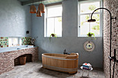 Free-standing wooden bathtub in bathroom of old farmhouse