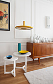 Colourful ceramics on set of white side tables