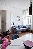 Esstisch und Sofa im Wohnraum mit Stuck und Kassettentür
