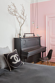 Piano against pink wall and panelled door in bedroom