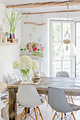 White hydrangeas on rustic wooden table and classic chairs below glass pendant lamp in dining room