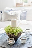 Candle in wreath of hydrangeas and candle lanterns on tray