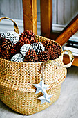 Basket with pine cones and star pendants as a Christmas decoration