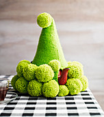 Green knitted hat with pompoms as a teapot warmer