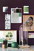 Selbstgemachte Leuchte unter der Glashaube vor violetter Bilderwand