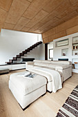 Pale sofa set in open-plan interior with zigzag staircase
