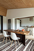 Rustic wooden table and classic chairs in front of open-plan kitchen