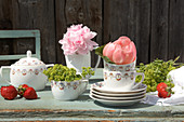 Peonies and ladies' mantel in coffee cups