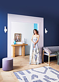 Young woman at the passage in the living room with blue wall