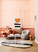 Designer armchairs and plexiglass placemat in the living room against an apricot-colored wall