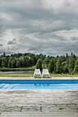 Two plastic chairs next to swimming pool with view of woods