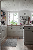 Panelled cabinets and wooden floor in pale country-house kitchen