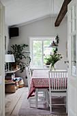 Blick ins ländliche Esszimmer mit Deckenbalken und Sprossenfenster