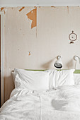 White bed linen on double bed below reading lamps and dreamcatcher on wall with peeling paint