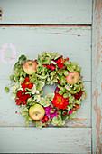 Late-summer wreath of hops, green hydrangeas, zinnias and apples