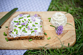 Bread spread with homemade chive-flower butter and sprinkled with chives