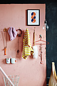 DIY coat rack made from large nails on pink wall