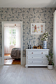 White-painted wooden chest of drawers against blue-and-white wallpaper
