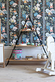 Pyramid shelves and rocking horse in child's bedroom with colourful wallpaper