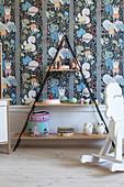 Pyramidenförmiges Regal und Schaukelpferd im Kinderzimmer mit bunter Tapete