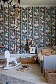 Rocking horse, gymnastic rings and wooden bed in child's bedroom with colourful wallpaper