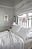 Vintage metal bed in front of window in romantic bedroom